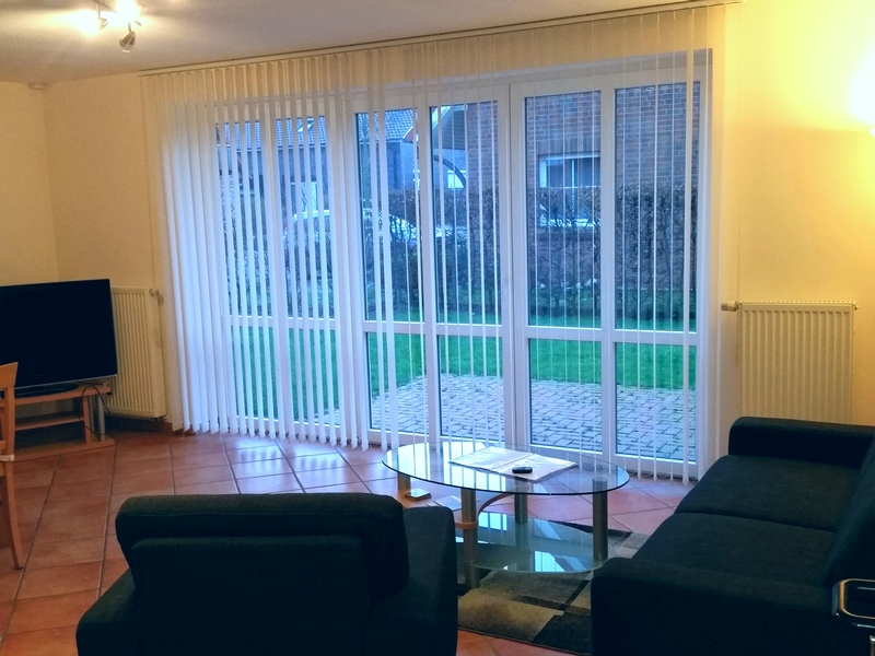 Wohnzimmer mit Fensterfront der Ferienwohnung Tönning von Ferienwohnungen Hass auf Fehmarn