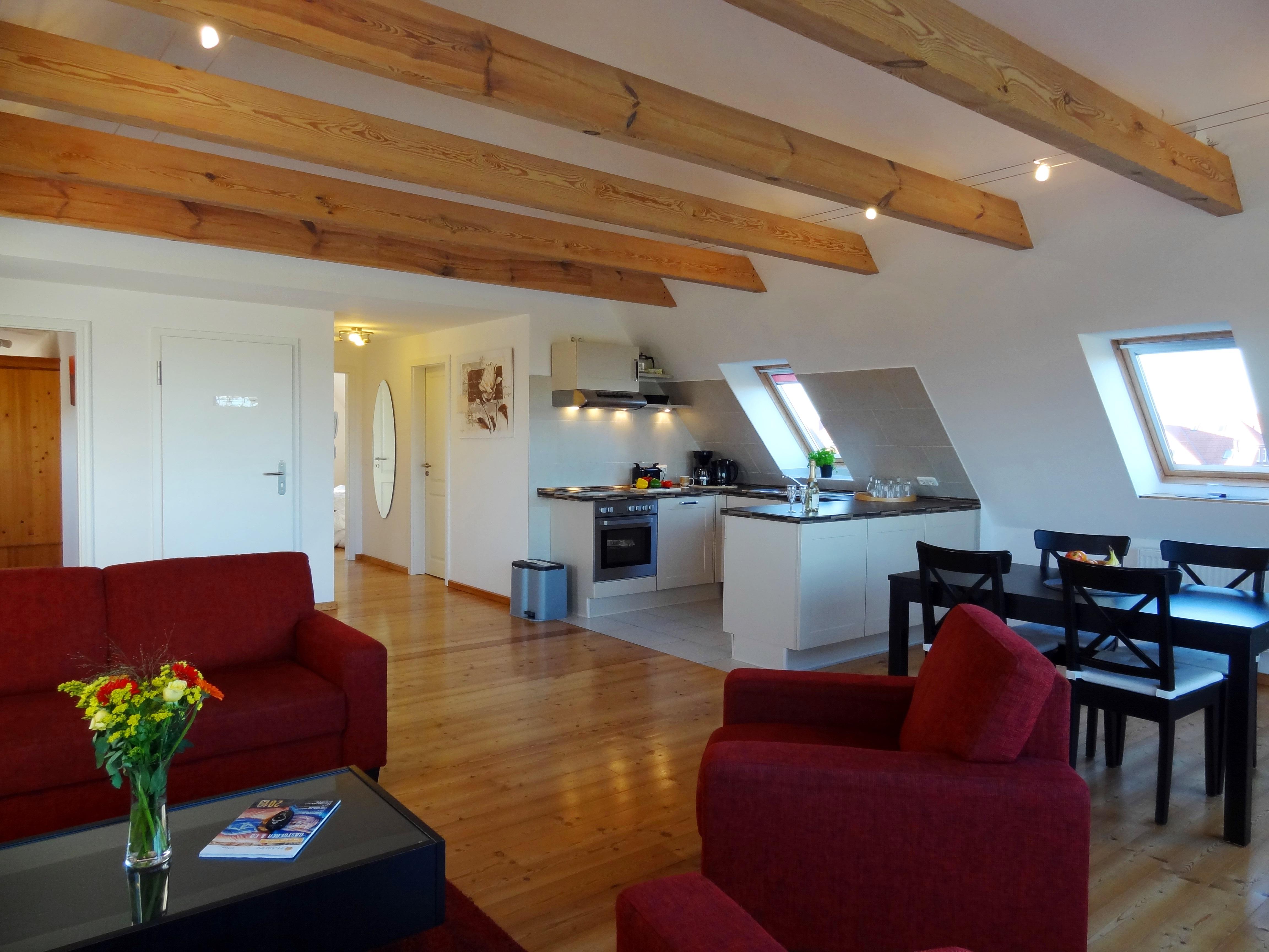 Wohnzimmer mit sichtbaren Dachbalken der Ferienwohnung Studio Seeblick von Ferienwohnungen Hass auf Fehmarn