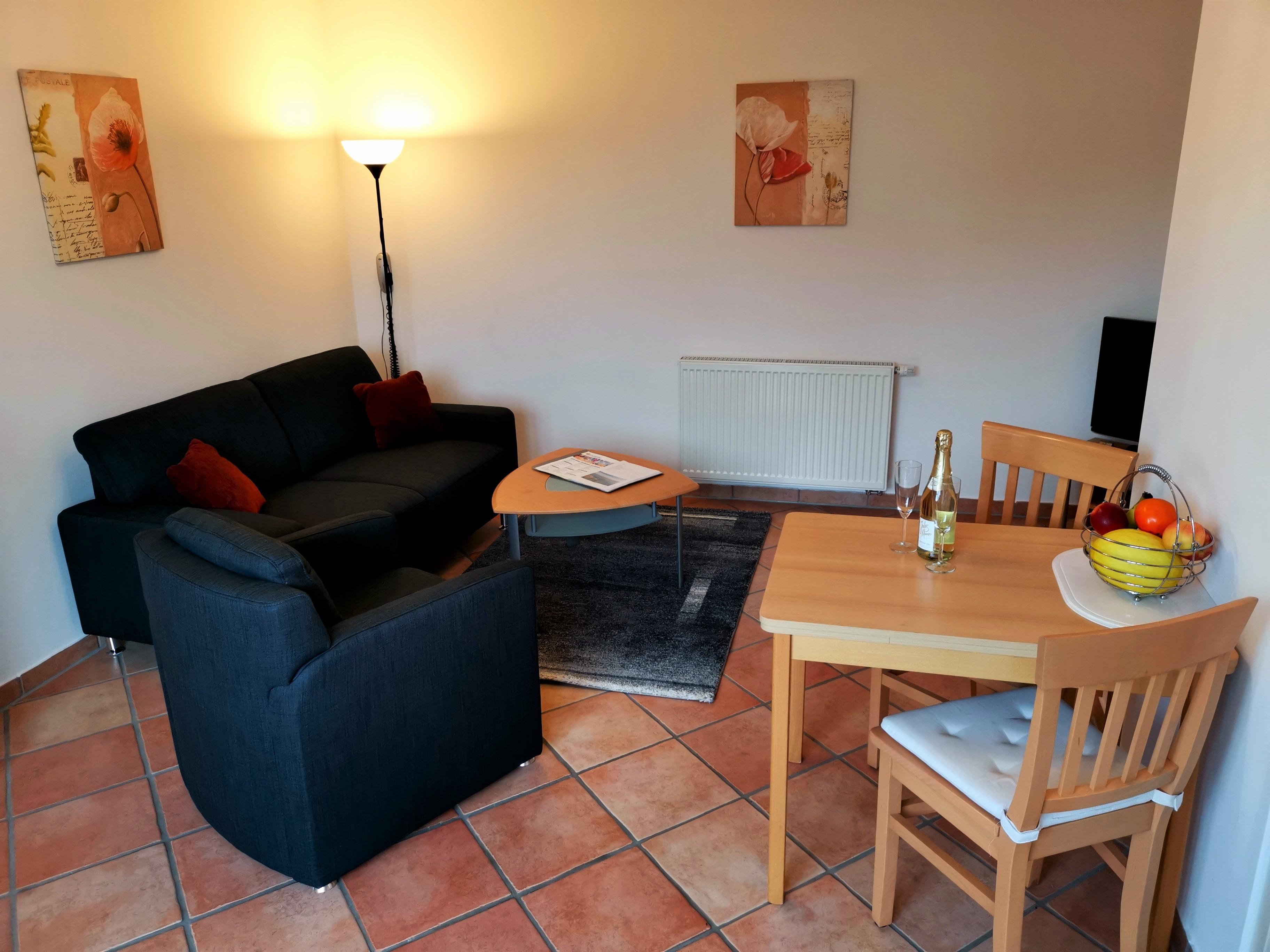Wohnzimmer der Ferienwohnung Heide mit Couch und Sessel und Essbereich von Ferienwohnungen Hass auf Fehmarn